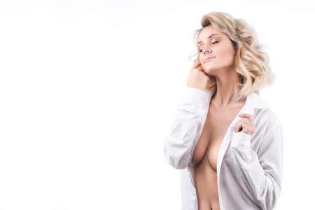 Sensueel portret van een groot breasted blondemeisje in een losgeknoopt wit die mensenoverhemd op een witte achtergrond wordt geïsoleerd. Ruimte kopiëren.