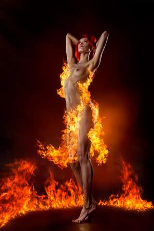Bailando pelirroja desnuda vestida con un vestido de fuego en el fondo de las llamas. Foto de archivo - 86129125
