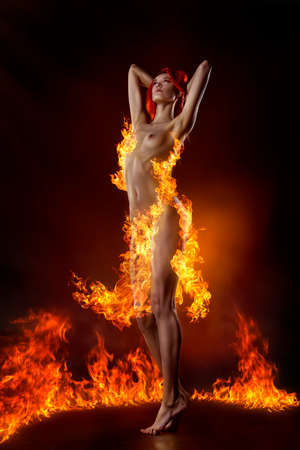 dansende naakte redhairmeisje gekleed in een vuurkleding op de achtergrond van vlammen. Stockfoto