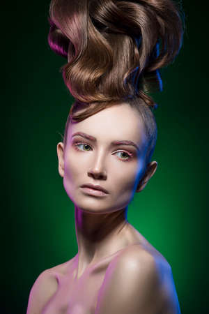 portrait of the beautiful girl with a vanguard hairstyle and a make-up on a green background. clear healthy skin Stock Photo