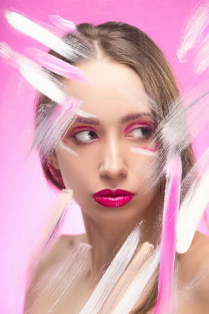 The beautiful girl with a vanguard make-up behind the glass covered with paint dabs on a pink background. Copy space. Advertising and Commercial Design. Healthy clean skin. Banque d'images