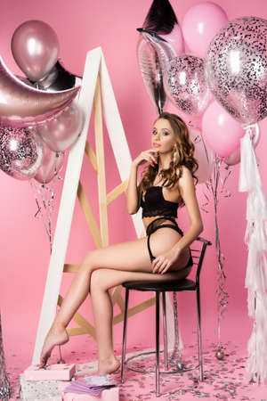 Beautiful sexy slim girl wearing black erotic underwear posing with helium balloons, gifts, confetti on a pink background. Party, holidays, new year, christmas. Advertising, fashion and commercial Design,