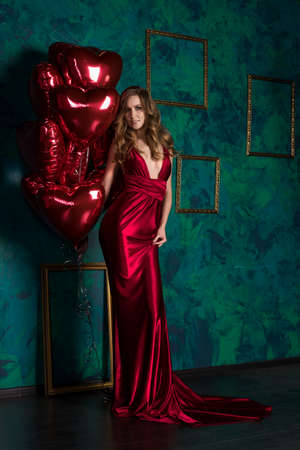 Beautiful tall slender blond girl wearing a deep neckline red satin dress posing with red balloons in the shape of a heart. Valentine's Day, holidays, party. Advertising, fashion and commercial Design Stock Photo