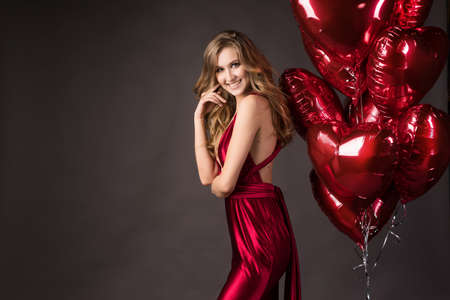 Beautiful tall slender blond girl wearing a deep neckline red satin dress posing with red balloons in the shape of a heart. Valentines Day, holidays, party. Advertising, fashion and commercial Design