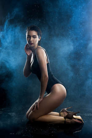 Beautiful asian wet big breasted girl wearing black swimsuit sits on on her knees on a dark background. Falling rain drops and artistic scenic smoke. Advertising, commercial design. Copy space.