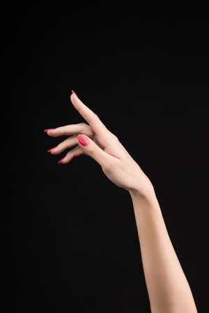 Closeup image of beautiful woman hand with pink manicure on the nails. Cream for palms, manicure and beauty treatment. Elegant and graceful arms with slender graceful fingers. Copy space. Isolated on black.