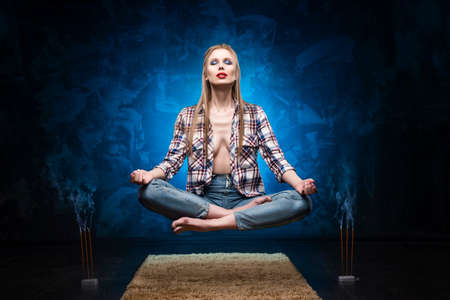 Beautiful red lips blonde big breast girl wearing an unbuttoned shirt and jeans meditates and levitates over the floor near smoky aromatic sticks. Copy space. Conceptual, advertising and commercial. Stock Photo
