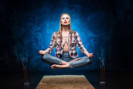 Labios rojos hermosos chica rubia de pecho grande con una camisa desabrochada y jeans medita y levita sobre el piso cerca de palos aromáticos ahumados. Copia espacio Conceptual, publicitario y comercial.
