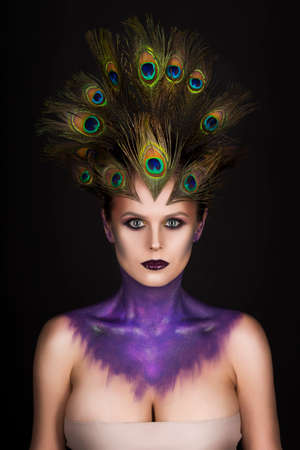 Beautiful big breast girl wearing peacock feathers in her hair and artistic violet shiny body art on her neck, vanguard makeup. Copy space. Black background. Conceptual, advertising and commercial.