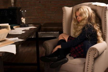 Belle écolière blonde aux cheveux longs est fatiguée sur une chaise à la table pleine de livres et de feuilles de texte dans une pièce intérieure vintage classique. Éducation scolaire. Copiez l'espace. Publicité, commercial Banque d'images - 98179586