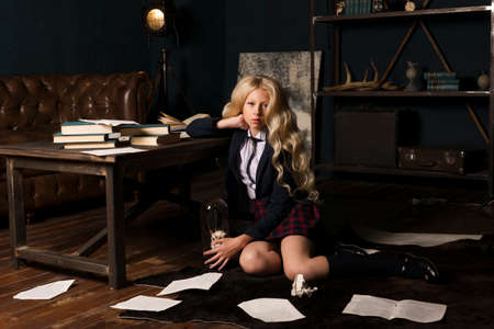Beautiful long haired blonde schoolgirl tiredly sits on on the floor at a table full books and sheets of text in a classic vintage interior room. School, education. Copy space. Advertising design.