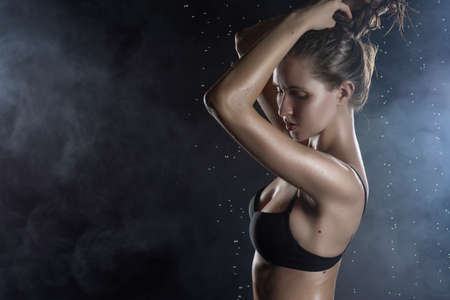 Beautiful wet blonde tall slim girl wearing a black lingerie posing in rain water drops in a studio on black background in a theatrical smoke. Smooth healthy wet skin. Copy space.