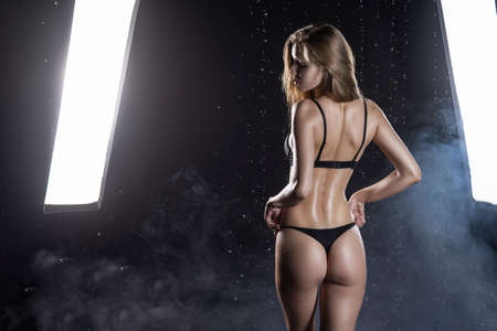 Beautiful wet blonde tall slim girl wearing a black lingerie poses from the back in rain water drops in a studio on black background and softbox lights in a theatrical smoke. Wet skin. Copy space.