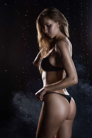 Beautiful wet blonde tall slim girl wearing a black lingerie poses from the back in rain water drops in a studio on black background in a theatrical smoke. Smooth healthy wet skin. Copy space.