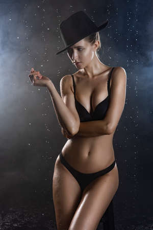 Beautiful wet blonde tall slim girl wearing a black lingerie and hat sits on the stool under the rain water drops in a studio on black in a theatrical smoke. Smooth healthy wet skin. Copy space.
