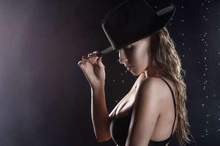 Beautiful wet blonde tall slim girl wearing a black lingerie and hat posing in rain water drops in a studio on black background in a theatrical smoke. Smooth healthy wet skin. Copy space. Фото со стока