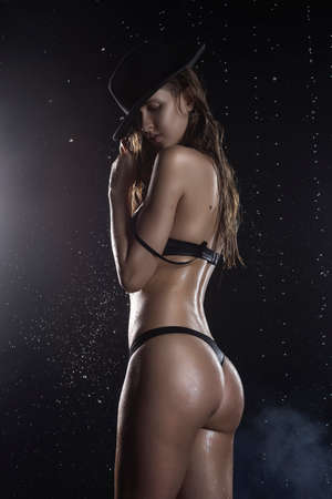 Beautiful wet blonde tall slim girl wearing a black lingerie and hat posing from side showing nice butt in rain drops in a studio on black in a theatrical smoke. Smooth healthy wet skin. Copy space.
