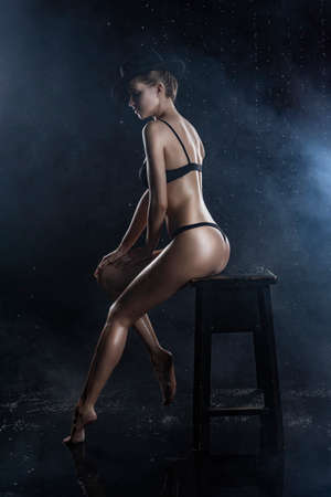 Beautiful wet blonde tall slim girl wearing a black lingerie and hat sits on the stool showing nice butt in rain drops in a studio on black in a theatrical smoke. Smooth healthy wet skin. Copy space. Фото со стока