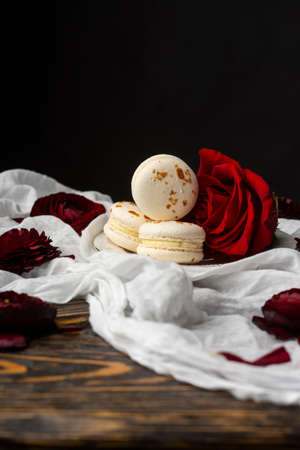 Three macaroons pastry lying on a plate surrounded by rose blossoms and rose petals on a wooden table covered with a crumpled white cloth. Still life.  Advertising, commercial design. Copy space.