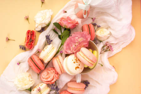 Pink and white macaroons cakes with big and small flower buds are decoratively laid on a white fabric and a cup on a yellow background. Copy space. Bakery, cooking, gifts, conceptual and advertising.