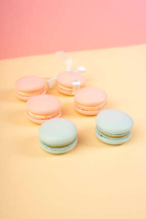 Blue and pink pastry macaroons, one of which is tied with a ribbon with a bow, arranged on a yellow and pink background. Copy space. Bakery, cooking, conceptual and advertising design. Фото со стока
