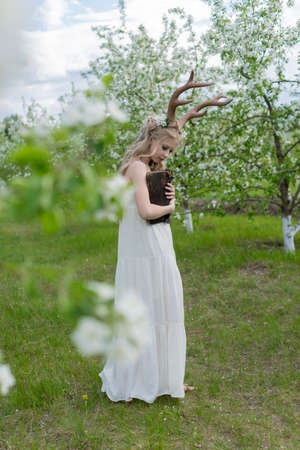 Teen beautiful blonde girl wearing white dress with deer horns on her head and white flowers in hair stays in a spring blooming garden clings to her closed antique book. Copy space.
