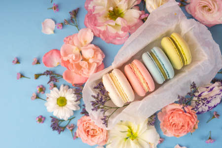 Multicolored macaroons cakes with big and small different flower buds in a gift box with wrapping paper on a blue background. Copy space. Bakery, cooking, gifts, conceptual and advertising.