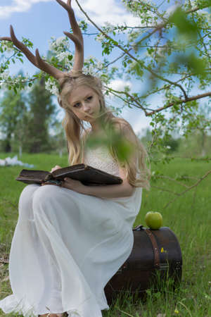 Teen beautiful blonde girl wearing white dress with deer horns on her head and white flowers in hair sits on a chest in a spring blooming garden and holds an antique book in her hands. Copy space. Фото со стока