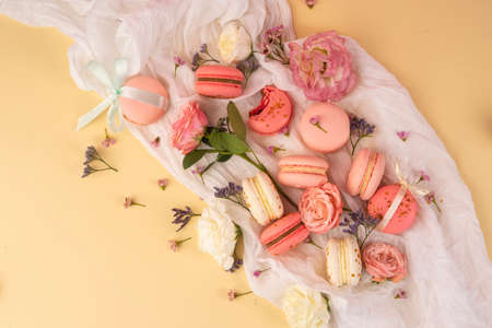 Pink and white macaroons cakes with big and small flower buds are decoratively laid on a white fabric on a yellow background. Copy space. Bakery, cooking, gifts, conceptual and advertising.