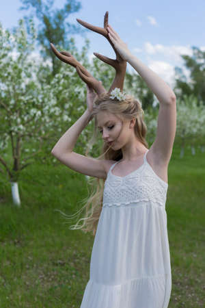 Teen beautiful blonde girl wearing white dress with deer horns on her head and white flowers in hair stays in a spring blooming garden and touching the horns with her hands. Copy space.