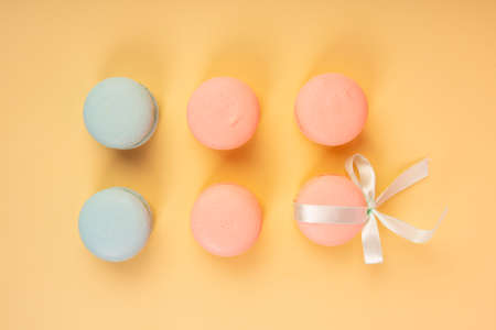 Blue and pink pastry macaroons, one of which is tied with a ribbon with a bow, arranged on a yellow background. Copy space. Bakery, cooking, conceptual and advertising design.
