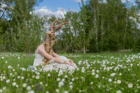 Teen beautiful blonde girl wearing white dress with deer horns on her head and white flowers in hair sits looking away on the grass among the white wildflowers and sniffing a flower. Copy space.