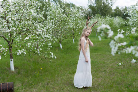 Teen beautiful blonde girl wearing white dress with deer horns on her head and white flowers in hair is standing near an antique chest in a spring blooming garden. Copy space,