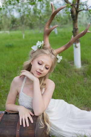 Teen blonde girl wearing white dress with deer horns on her head, white butterfly and white flowers in her hair sits on the grass leaning on the ancient chest in a blooming garden. Copy space. Фото со стока