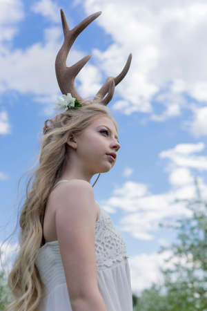 Teen beautiful blonde girl wearing white dress with deer horns on her head and white flowers in hair stays on the background of the blue sky and clouds and looks into the distance. Copy space. Фото со стока
