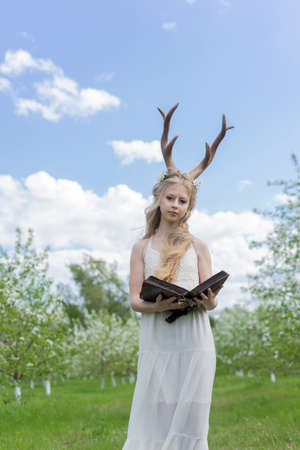 Teen beautiful blonde girl wearing white dress with deer horns on her head and white flowers in hair stays in a spring blooming garden holds an open antique book in her hands. Copy space.