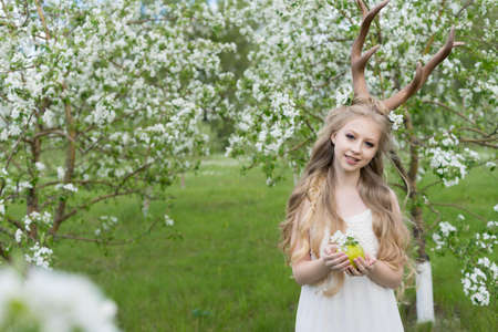 Teen beautiful blonde girl wearing white dress with deer horns on her head and white flowers in hair stays in a spring blooming apple garden and holds a green apple in her hands. Copy space.