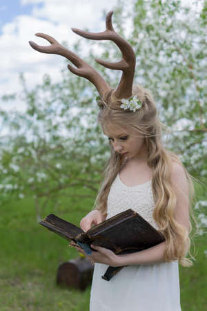 Teen beautiful blonde girl wearing white dress with deer horns on her head and white flowers in hair stays in a spring blooming garden carefully reads the ancient antique book. Copy space.