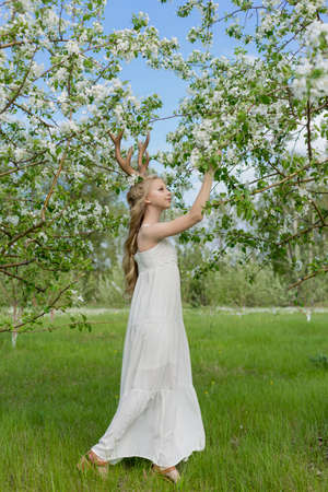 Teen beautiful blonde girl wearing white dress with deer horns on her head and white flowers in hair stays in a spring blooming garden of trees covered with white flowers. Copy space.