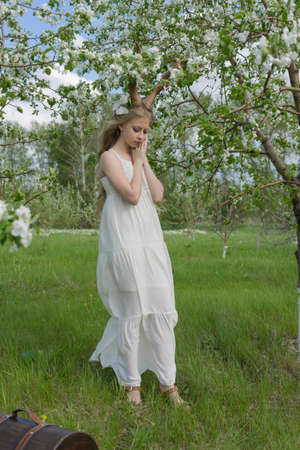 Teen beautiful blonde girl wearing white dress with deer horns on her head, white butterfly and white flowers in her hair touches her face in a spring blooming garden. Copy space.