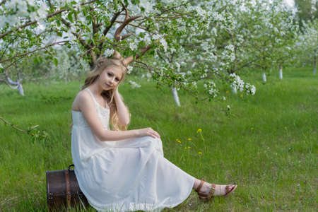 Teen beautiful blonde girl wearing white dress with deer horns on her head and white flowers in hair is pensive sadly sits on an antique chest in a spring blooming garden. Copy space.