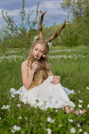 Teen beautiful blonde girl wearing white dress with deer horns on her head and white flowers in hair sits with her eyes closed on a grass among the white wildflowers and sniffing a flower. Copy space. Фото со стока