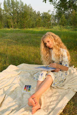 Beautiful charming barefoot long curly blonde hair teenage girl wearing a long light dress outdoors on a picnic paints with watercolor drawing sitting on a blanket on the grass. Copy space. Lifestyle.