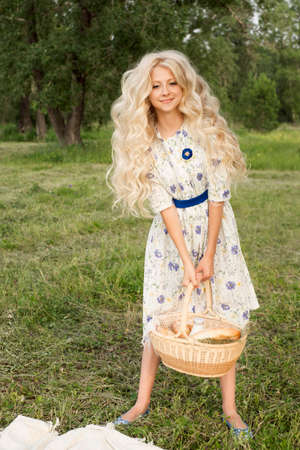 Beautiful charming long curly blonde hair teenage girl wearing a long light dress outdoors on a picnic smiles and holds a big basket full of food and a bottle of milk. Copy space. Lifestyle Stock Photo