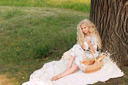 Hermosa encantadora encantadora rubia de pelo largo y rizado adolescente con un vestido largo y ligero al aire libre en un picnic se sienta debajo de un gran árbol junto a una canasta llena de comida y una botella de leche. Copia espacio Estilo de vida