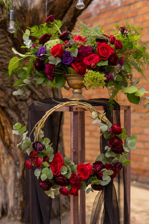 An old vase with roses and green leaves and a wreath of red roses stand on a wooden stand decorated with a black veil against the background of a tree. Decoration, gothic wedding. Copy space.