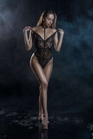 Beautiful wet slim girl wearing a black translucent lingerie posing in rain water drops in a studio on black background in a theatrical smoke. Smooth healthy wet skin. Copy space. Фото со стока