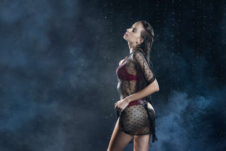 Young wet slim girl wearing a red lingerie and black translucent veil posing sideways in rain water drops in a studio shows her beautiful butt on black in a theatrical smoke. Healthy skin. Copy space 写真素材