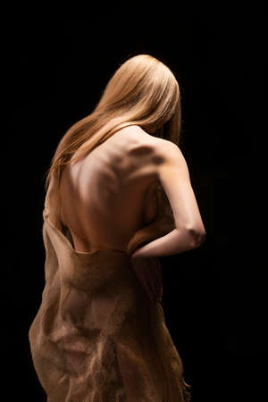 A beautiful young big breasted naked blonde girl, covering her nakedness with a cloth of burlap. Isolated on a black background. Conceptual artistic photo. Smooth healthy wet skin. Copy space