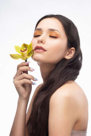 A beautiful brunette nude shoulders girl sensually holds a flower of an orchid in her hands. Nude make-up. Healthy smooth skin. Isolated on white background. Copy space. Commercial and advertising. Stockfoto